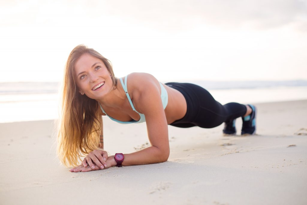 A women holding a plank position on the beach